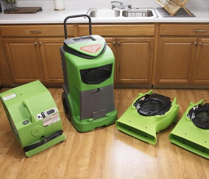 SERVPRO equipment lined up on a vinyl faux wood floor.
