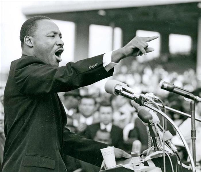 Martin Luther King Jr. standing at a podium mid-speech, his finger pointing straight ahead with bold declaration.